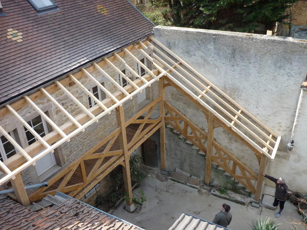 Auvent et terrasse avec croix de Saint-André, dans une cour intérieure.